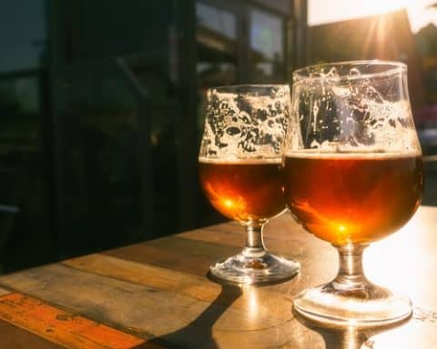 Closeup of two glasses of beer on terrace table with evening sun shining through them. Relaxation, food and drink concept with copy space.